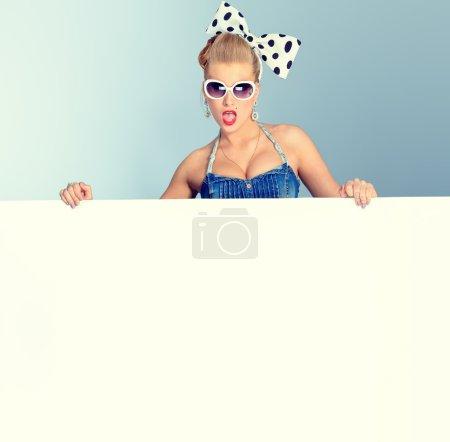 Photo pour Belle jeune femme avec pin up maquillage et de coiffure qui pose en studio avec tableau blanc. - image libre de droit