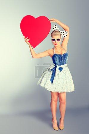 Photo pour Belle jeune femme avec pin up maquillage et de coiffure qui pose en studio avec coeurs rouges. - image libre de droit