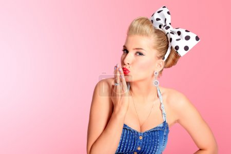 Photo pour Belle jeune femme avec pin up maquillage et coiffure posant sur fond rose. - image libre de droit