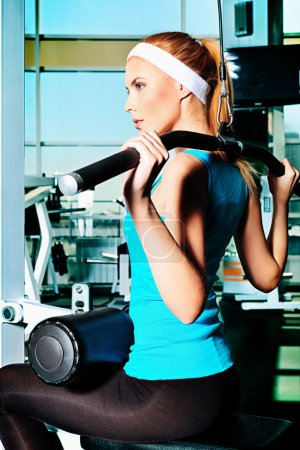 Photo for Young sporty woman doing exercises in the gym centre. - Royalty Free Image