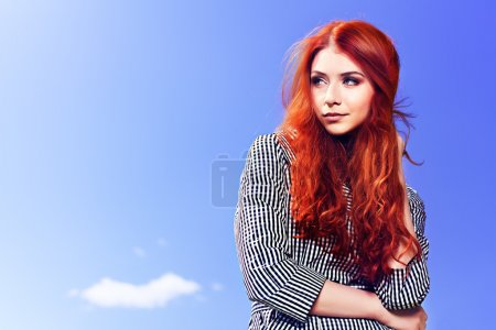 Photo for Portrait of a beautiful red-haired young woman over blue sky. - Royalty Free Image