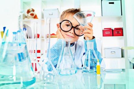 Photo pour Garçon mignon fait des expériences scientifiques dans un laboratoire. éducation - image libre de droit