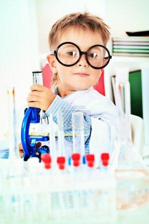 Photo pour Mignon garçon fait des expériences scientifiques dans un laboratoire. Éducation . - image libre de droit