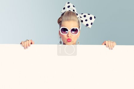 Photo for Beautiful young woman with pin-up make-up and hairstyle posing in studio with white board. - Royalty Free Image