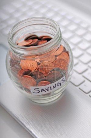 Foto de Un concepto de trabajar mucho para ahorrar un poco de dinero que está representado por un teclado de computadora y monedas en un frasco - Imagen libre de derechos