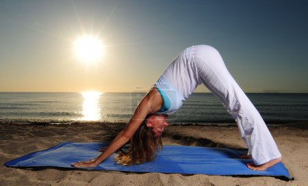 Photo for Woman doing Downward Facing Dog (Adho Mukha Svanasana) yoga pose on beach during sunrise - Royalty Free Image
