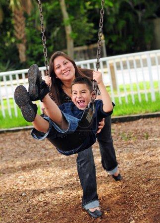 Mom pushing son on swing