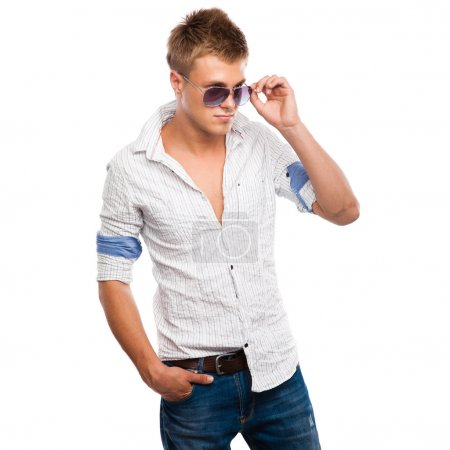 Handsome young man in jeans, light shirt and sunglasses