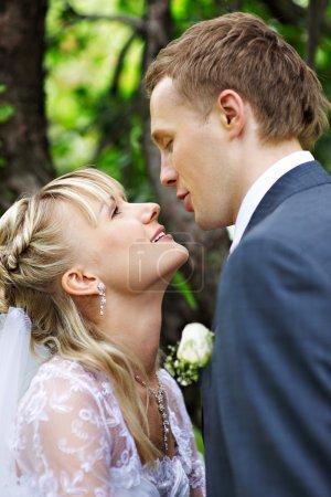 Happy bride and groom in wedding walk in park
