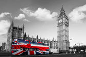 Big Ben with city bus covered flag of England, London, UK