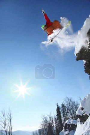 Snowboarder springt gegen blauen Himmel