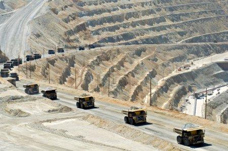Photo pour Une ligne de camions à benne à monstre transportent 250 tonnes de roche hors d'une mine à ciel ouvert . - image libre de droit