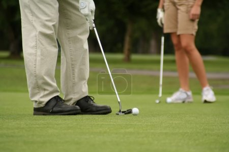 Man putting, woman in background, shallow dof