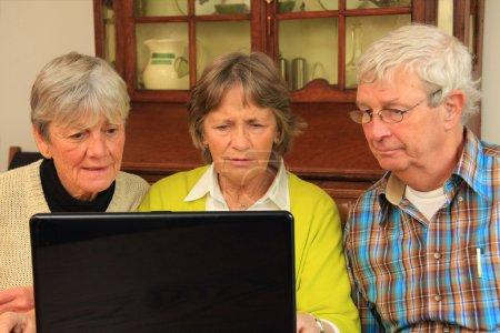 Photo pour Trois personnes âgées actives surfant sur Internet . - image libre de droit