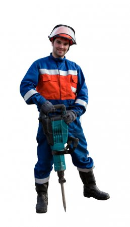 Worker in overalls with an electric hammer
