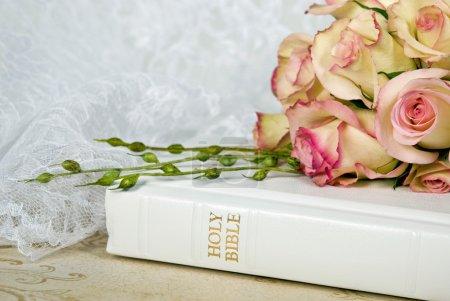 Wedding roses on white Bible....