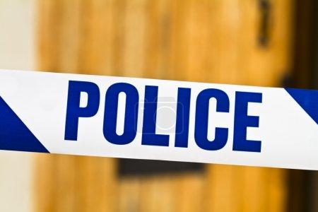 Photo pour Gros plan du ruban de police à travers une porte ouverte - image libre de droit