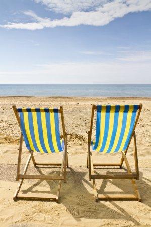 Photo pour Deux chaises longues sur la plage de bournemouth, dorset, Royaume-Uni sur une journée d'été ensoleillée lumineux - image libre de droit