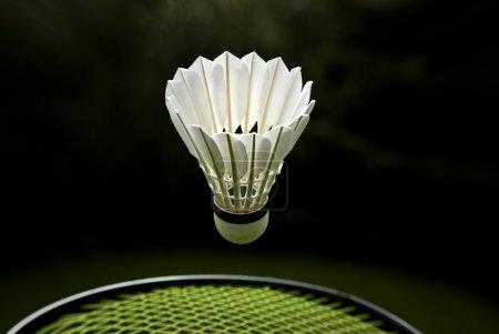 Photo pour Navette badminton plumes d'oie et raquette sur fond sombre . - image libre de droit