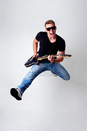 Photo pour Rockstar bondissant avec guitare - image libre de droit