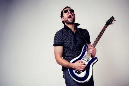 Photo pour Joueur de guitare. Rockstar jouant à la guitare. lunettes de soleil - image libre de droit