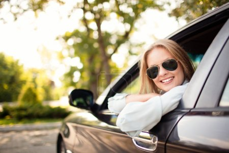 Young woman in her new car