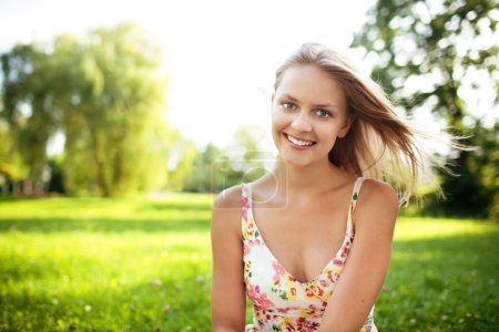 Beautiful young woman sitting on grass at park smiling