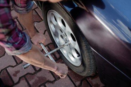 Photo pour Mécanicien de voiture roue de réparation avec clé - image libre de droit