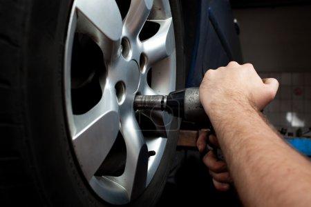 Photo pour Mécanicien automobile, changement de roue sur la voiture avec une clé pneumatique. - image libre de droit