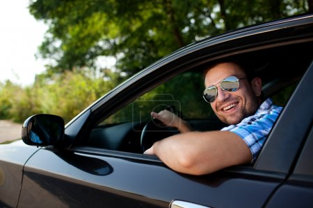 Photo for Portrait of young handsome man smiling in his own car - Royalty Free Image