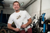 Happy car mechanic standing with wrench tool