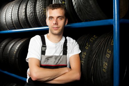 Young mechanic standing next to tire shelves in tire store