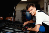 Auto mechanic repairing car