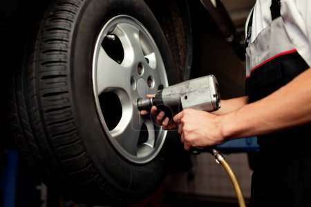 Photo for Auto mechanic changing car wheel - Royalty Free Image