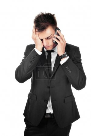 Photo for Portrait of sad, depressed young businessman talking on phone - Royalty Free Image