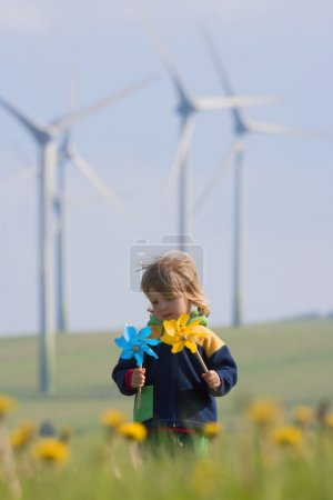 Photo for Boy with long hair holding pinwheels standing in front of wind turbines - Royalty Free Image