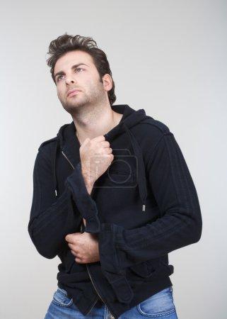 Photo pour Portrait d'homme en pull noir levant les yeux - isolé sur gris - image libre de droit