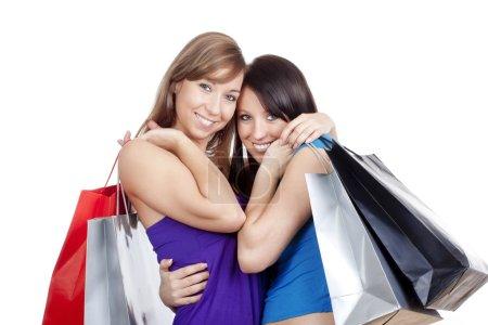 Photo pour Deux jeunes filles heureuses avec des sacs à provisions souriant - isolé sur blanc - image libre de droit