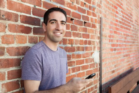 Guy leaning on wall with phone
