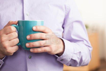 Man holding blue coffee mug detail