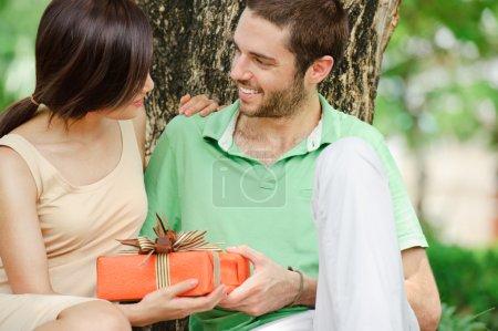 Photo pour Jeune homme donnant un cadeau à sa petite amie - image libre de droit
