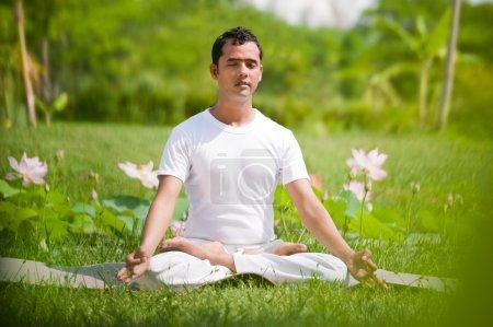 Photo pour Jeune homme assis en position lotus à l'extérieur dans un environnement naturel - image libre de droit