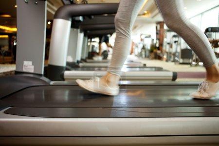Photo pour Gros plan des jambes féminines faisant de l'exercice sur une machine cardio - image libre de droit