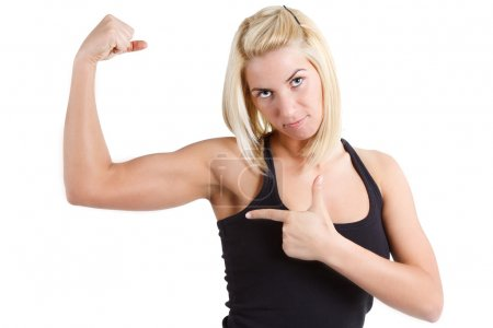 Sportswoman pointing at her muscle