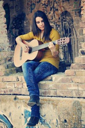 Photo pour Une adolescente jouant de sa guitare en descente de bâtiment - image libre de droit