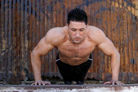 Young caucasian male in sportswear doing push ups