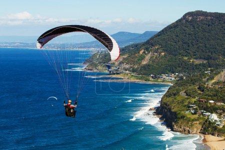Photo pour Parachutisme sur l'océan bleu profond et vue panoramique sur l'escarpement côtier à Stanwell tops NSW Australie - image libre de droit