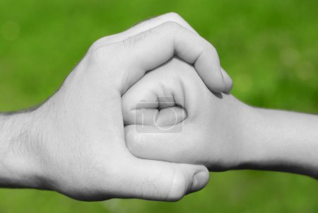 Black and white hand holding or stopping a fist in...