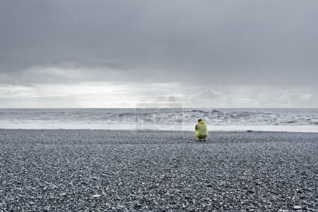 Photo for Man in a yellow rain coat kneeling down at the ocean - Royalty Free Image