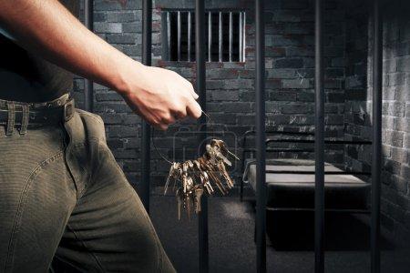 Prison guard with keys walking outside dark prison cell